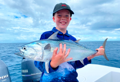 2021 fishing news hervey bay - boy holding a fish caught in the waters of hervey bay