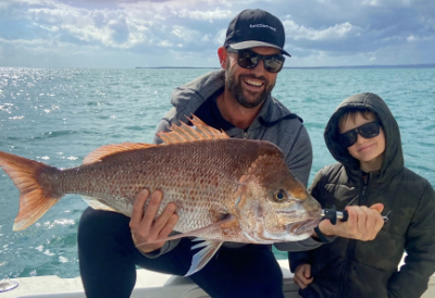 june july fishing report father and son holding large fish on fishing charter hervey bay